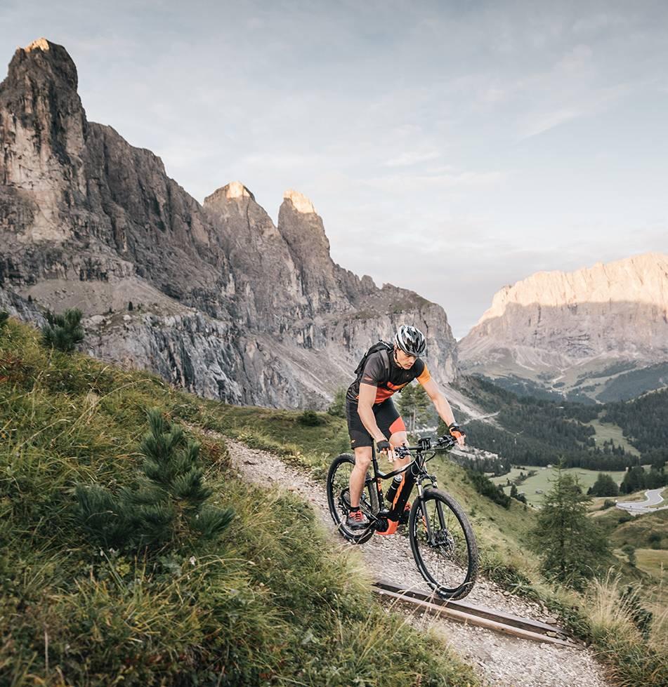 Ein Mann ist gerade auf seinem E-Mountainbike auf den Weg ins Tal.