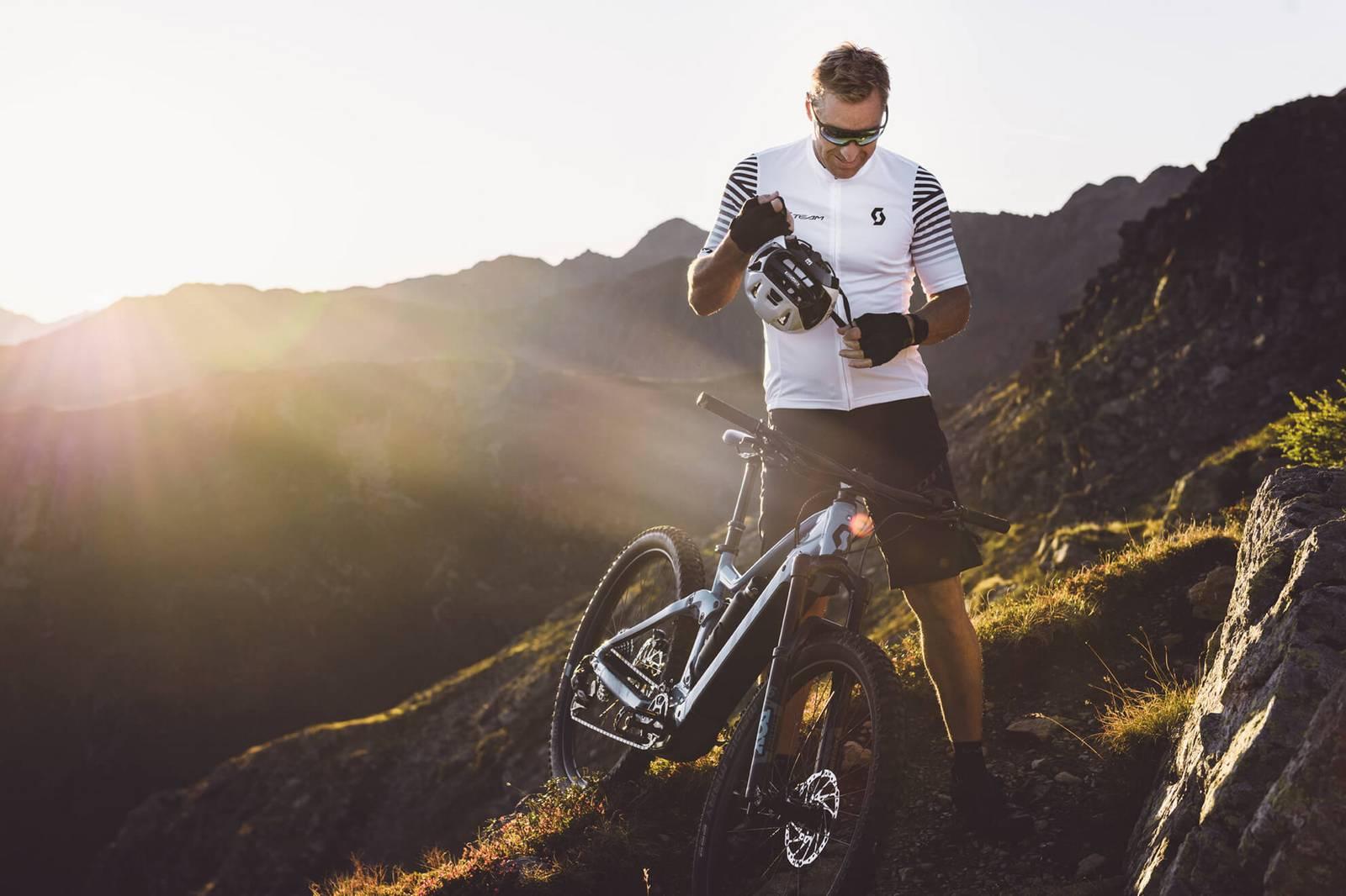 Der E-Biker setzt sich den Helm auf.