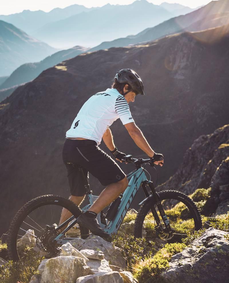 Ein Mountainbiker ist auf seinem E-Bike gerade an einer schmalen Stelle am Berg unterwegs.