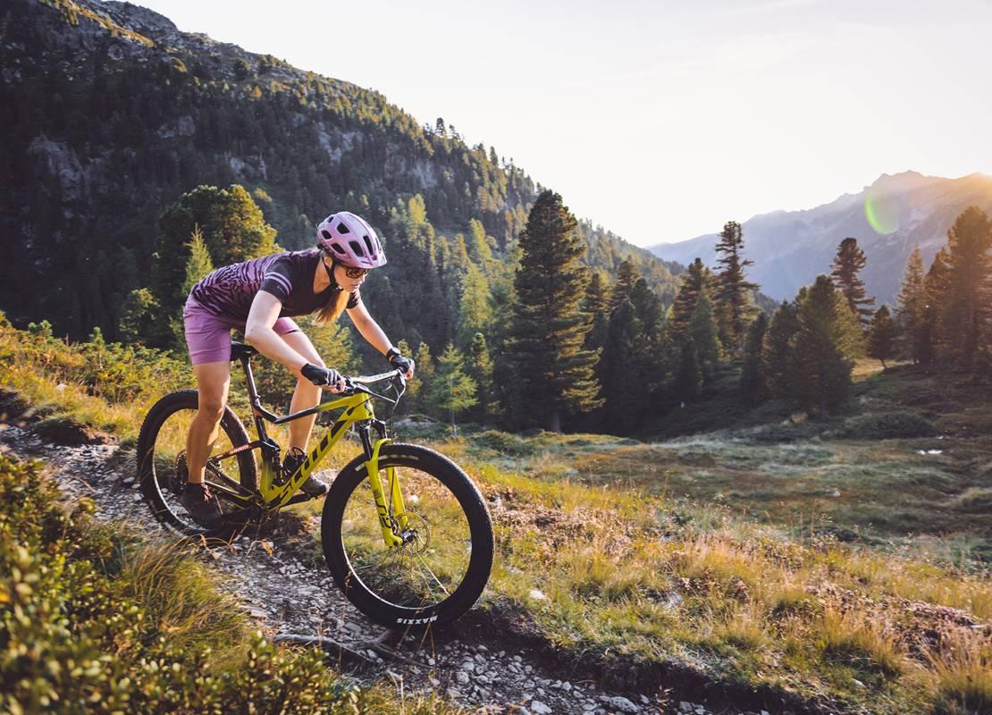 Eine Mountainbikerin ist gerade am Weg ins Tal, bei abendlicher Stimmung.
