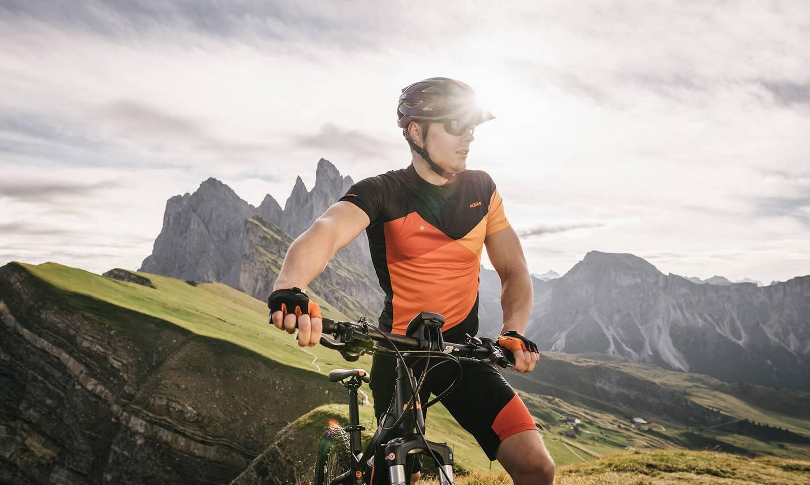 Ein Mountainbiker steht seitlich vor der Sonne.