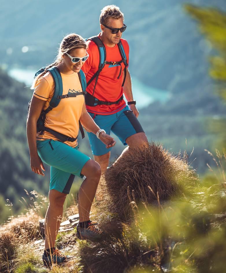 Zwei Freunde sind am gerade am Weg auf einem Gipfel. Im Hintergrund sind Berge und ein See.