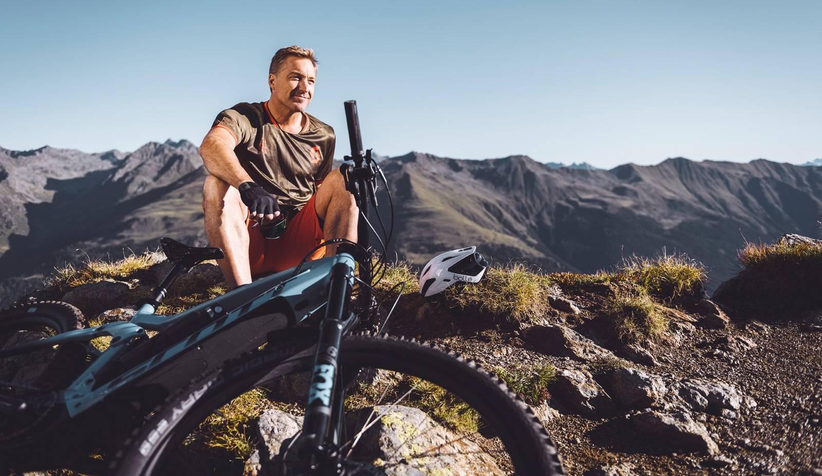Hans Knauß genießt die Aussicht mit seinem E-Bike am Berg.
