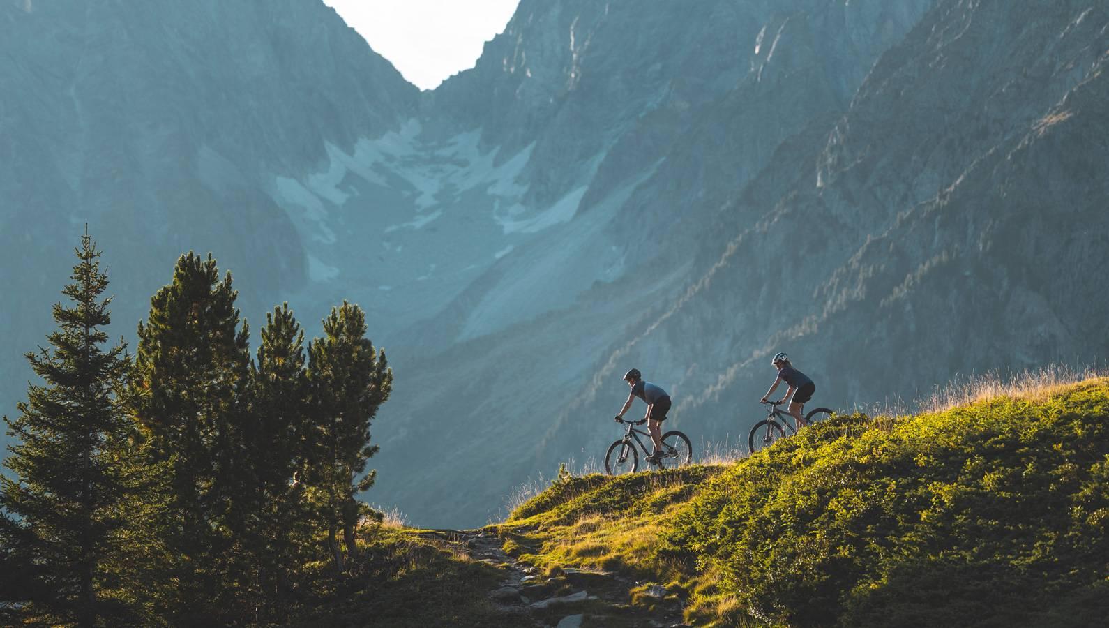 Traumhafte Bergkulisse in der 2 Biker am Weg Richtung Tal sind.