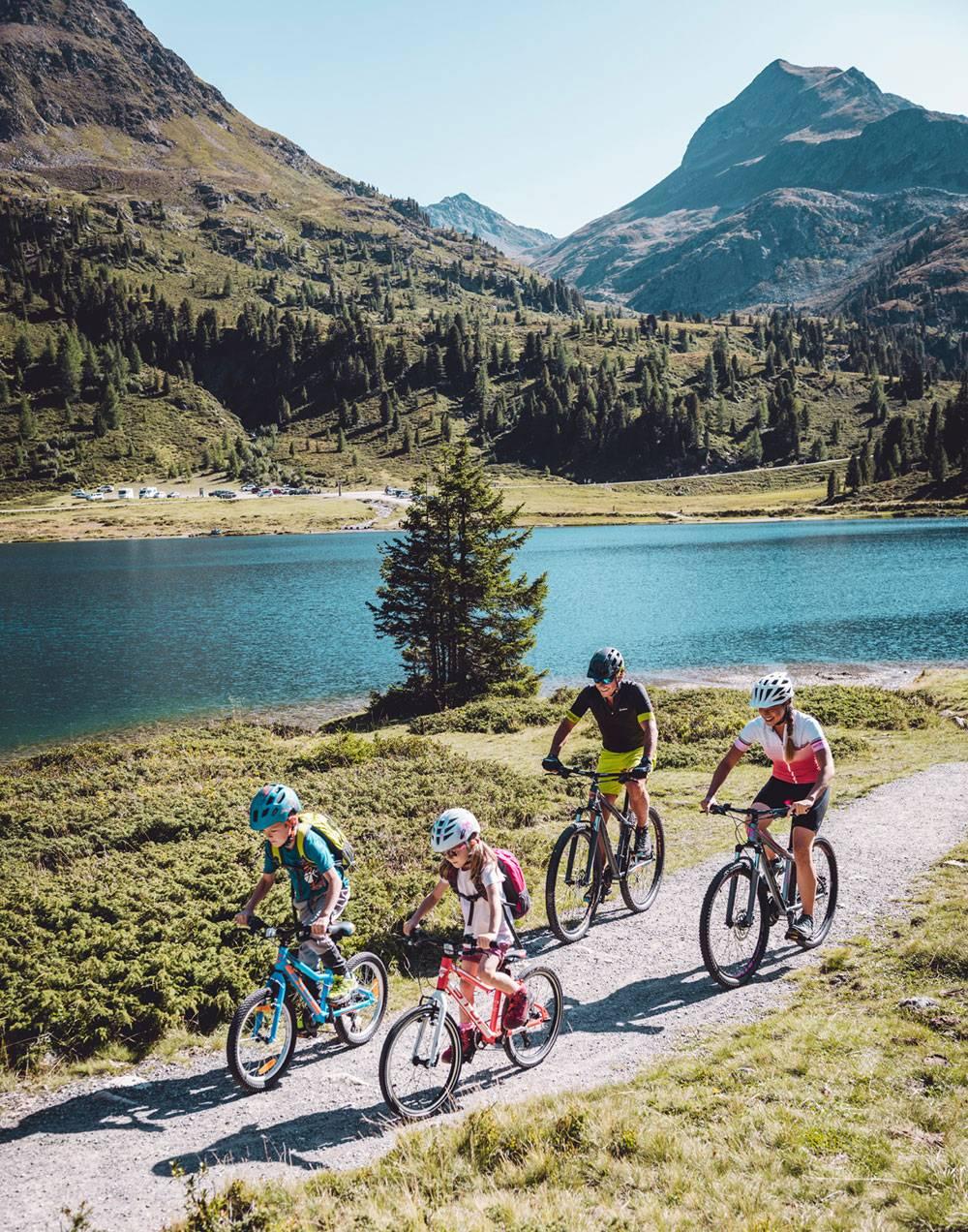 Eine vierköpfige Familie die mit ihren Bikes auf einer Forststraße unterwegs ist. Im Hintergrund Berge und ein See.