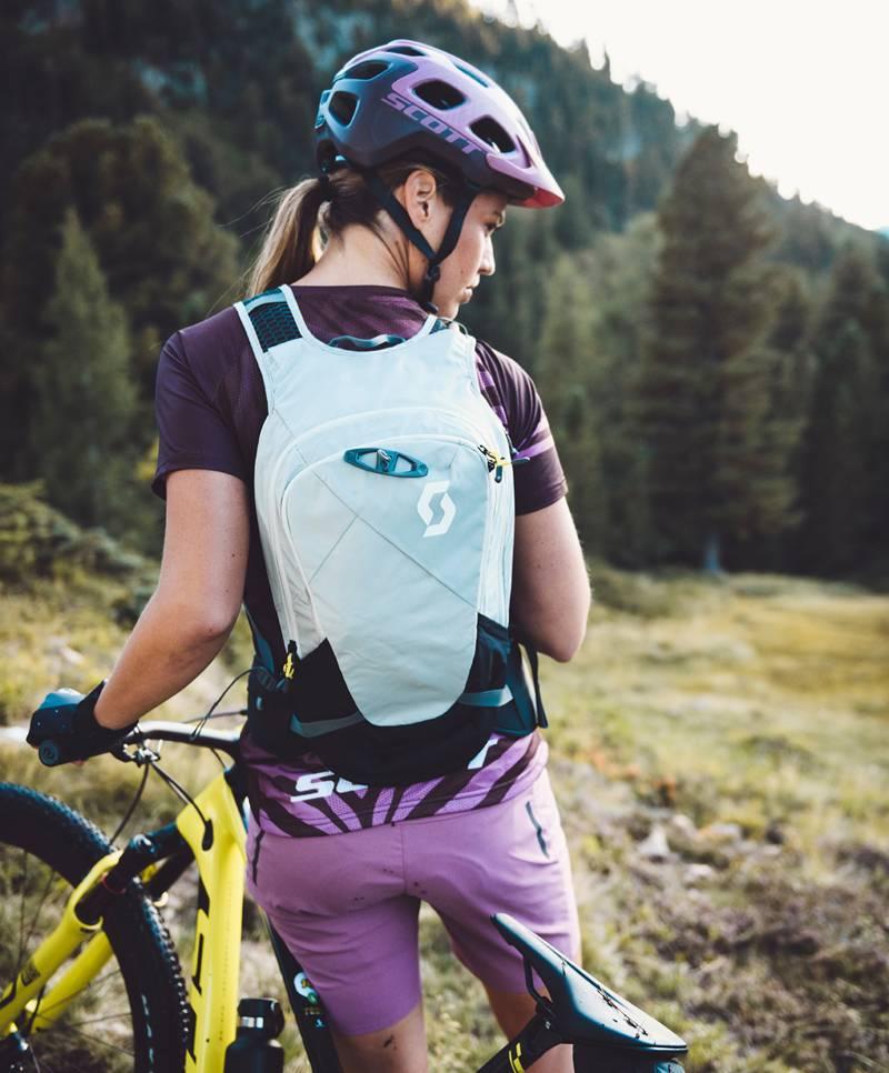 Eine Bikerin steht mit den Rücken zur uns und hält ihr Rad auf der linken Seite. Fokus ist hier auf dem Helm und den Rucksack.