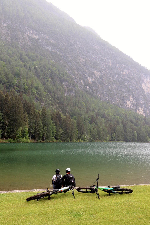 Ein Biker genießt die Rast beim Ufer eines Bergsees.