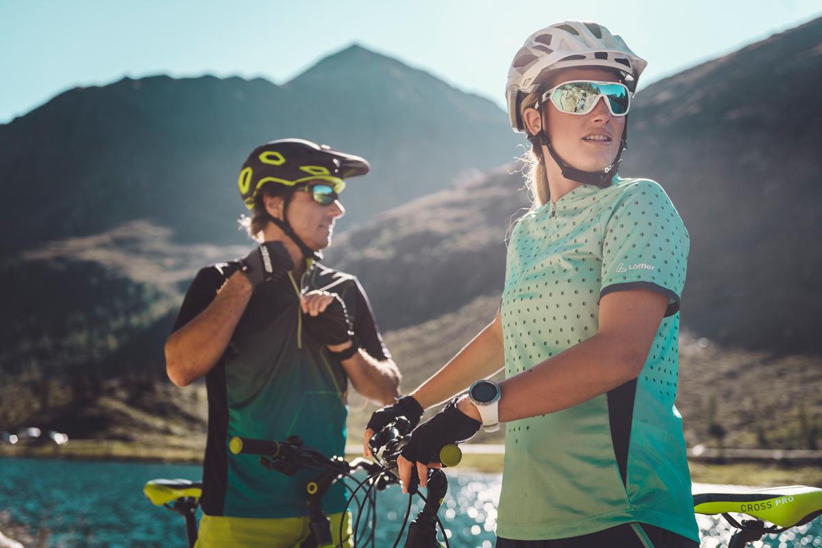 Zwei Biker machen gerade Pause. Im Hintergrund sind Berge und ein See.