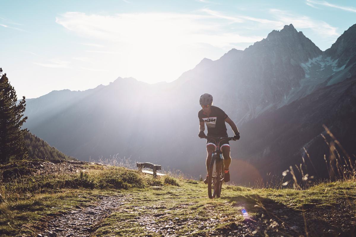 Ein Mountainbiker der gerade eine Anhöhe überwunden hat. Im Hintergrund eine abendliche Berglandschaft.
